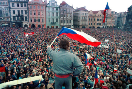 "NOTE: The sign at right that is partially covered by the waving flag reads ""Fuck You"" in Czech.  Prague, Czechoslovakia. A crowd of approximately 500,000 people take part in an anti-Soviet protest in Prague's Old Town Square, in late February of 1990. The Czech public had become restless because it that been 3-months since the Soviets were forced to relinquish control, yet they still hadn't withdrawn from the country. November 17th marked the beginning of the 6-week-long, 20th anniversary of the Velvet Revolution. Photo by Deirdre Hamill/Quest Imagery"